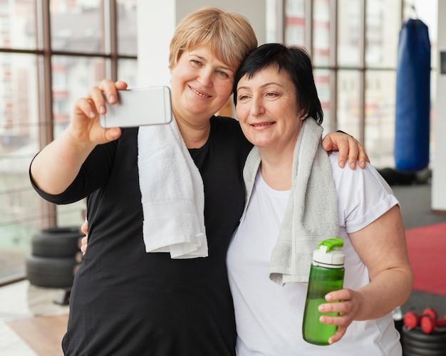 Ältere frauen, die selfie im fitnessstudio nehmen