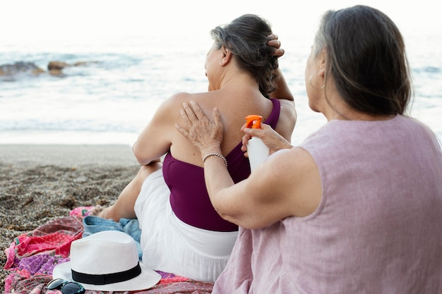 Ältere frauen, die sonnencreme auf der rückseite am strand auftragen