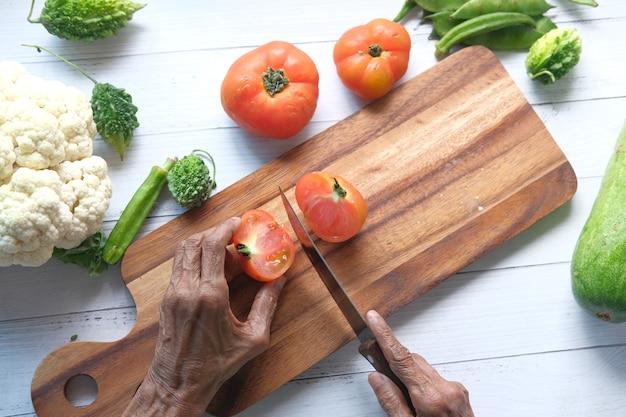 Ältere frauen, die tomaten auf einem schneidebrett von oben nach unten schneiden