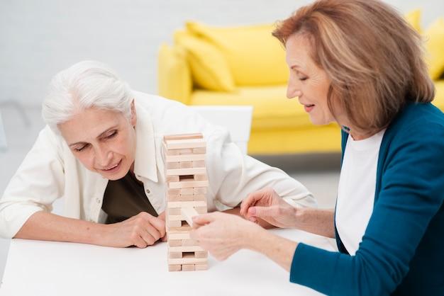Ältere frauen, die zusammen jenga spielen