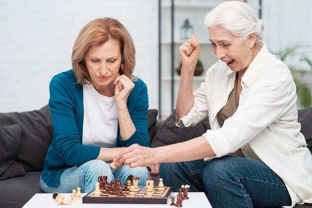 Ältere frauen, die zusammen schach spielen
