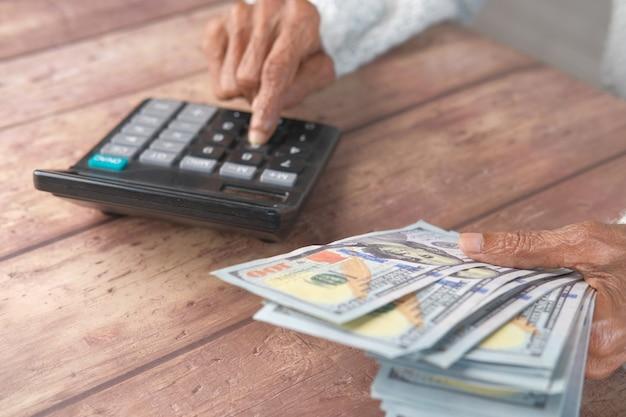 Ältere frauen halten uns dollar bargeld und verwenden taschenrechner selektiven fokus