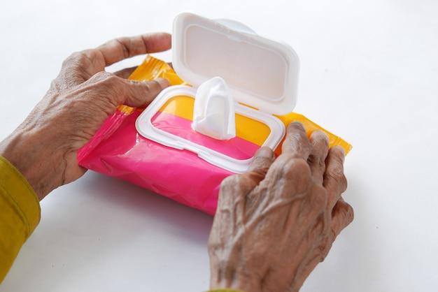 Ältere frauen hand mit reinigungsfeuchttüchern paket auf weiß