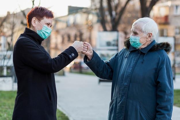 Ältere frauen mit medizinischen masken stoßen in der stadt gegen die fäuste, um sich gegenseitig zu grüßen