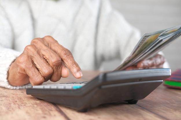 Ältere frauen übergeben unter verwendung des taschenrechners und halten bargeld auf tisch