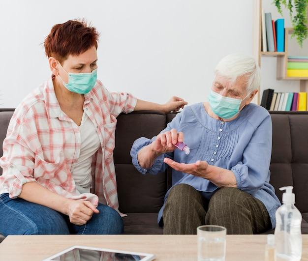 Ältere frauen zu hause desinfizieren ihre hände