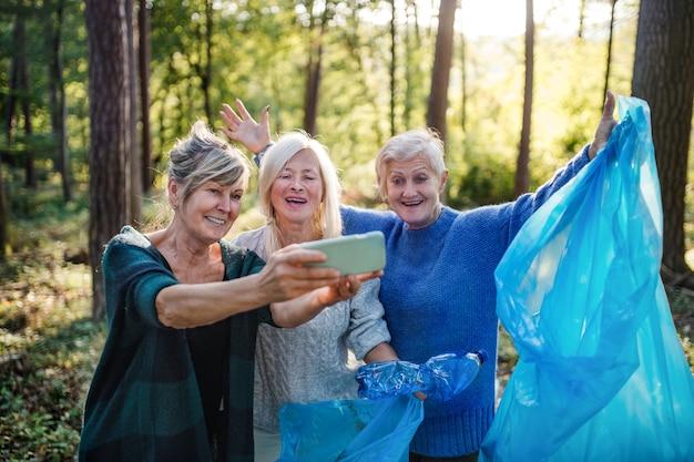 Ältere frauenfreunde, die draußen im wald abfall aufheben und selfie nehmen. ein plogging-konzept.