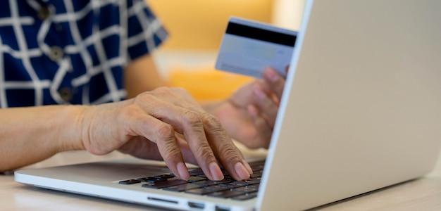 Ältere frauenhand, die laptop verwendet und kreditkarte hält, um rechnungen vom online-einkauf zu bezahlen