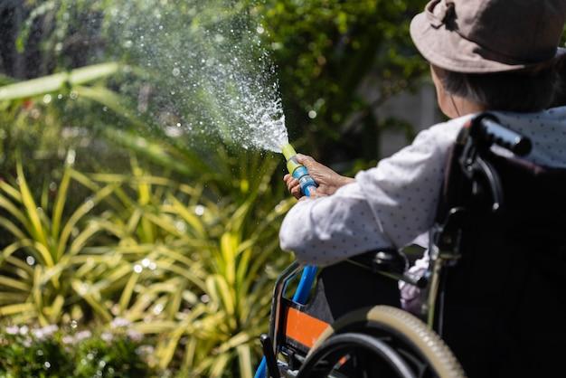 Ältere frauenhand, die schlauchsprüher hält und pflanzen im hinterhof gießt