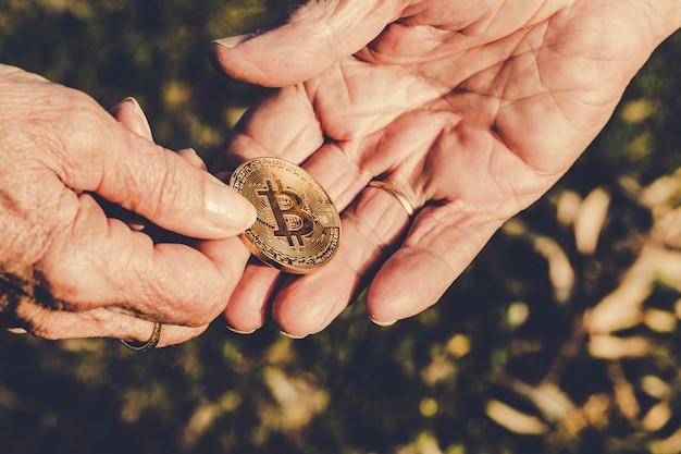 Ältere frauenhand hält die bitcoin münze, die zur hand des älteren mannes auf grüner natur gibt