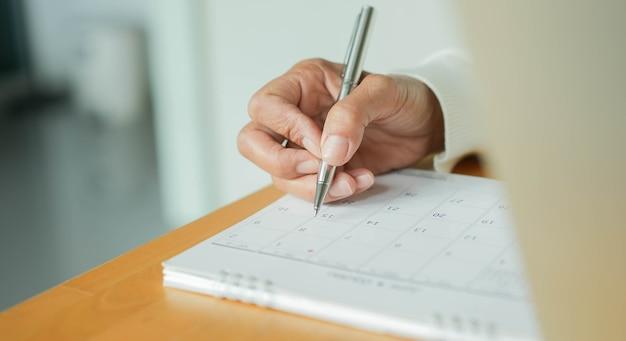 Ältere frauenhand mit stift, um einen termin im kalender zu markieren oder zu vereinbaren