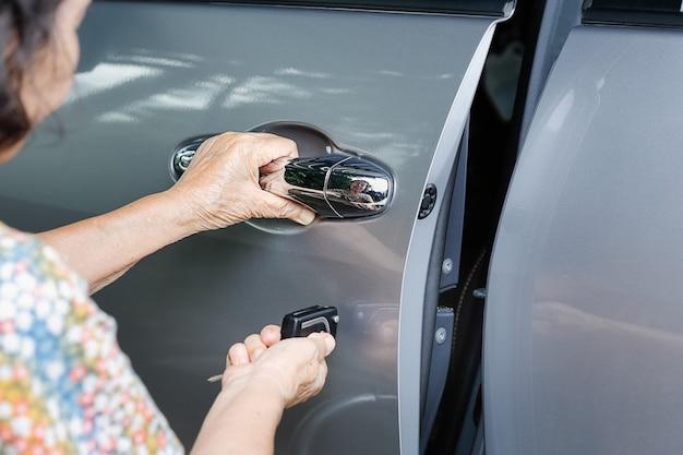 Ältere frauenhand öffnen das auto auf wichtigen autoalarmsystemen