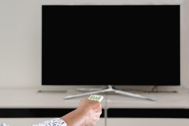 Ältere frauenhandgrifffernbedienung des fernsehkastens aufpassend, leere anzeige