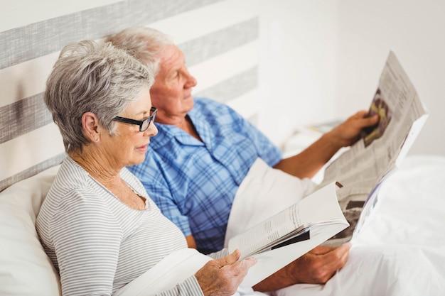 Ältere frauenlesezeitschrift und zeitung des älteren mannes leseauf bett