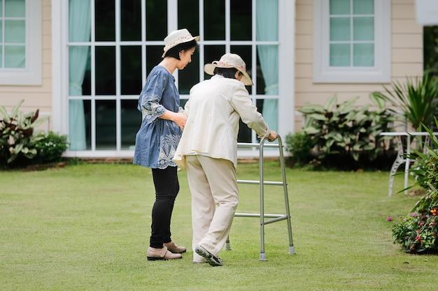 Ältere frauenübung, die mit tochter im hinterhof spazieren geht