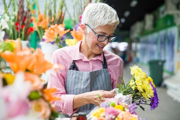 Ältere frauenverkäufe blüht auf lokalem blumenmarkt