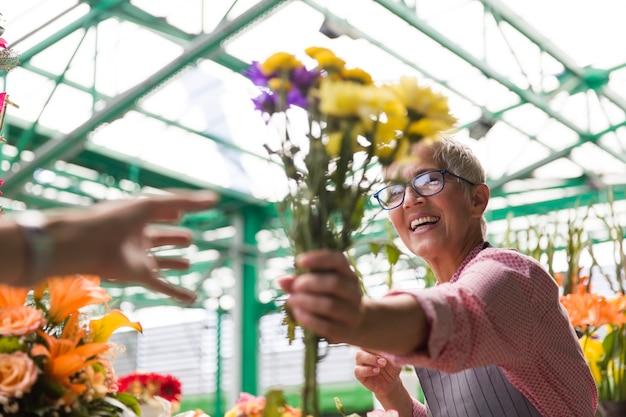 Ältere frauenverkaufsblumen auf lokalem blumenmarkt