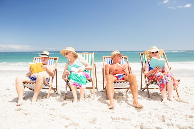 Ältere freunde, die bücher auf strandstühlen lesen