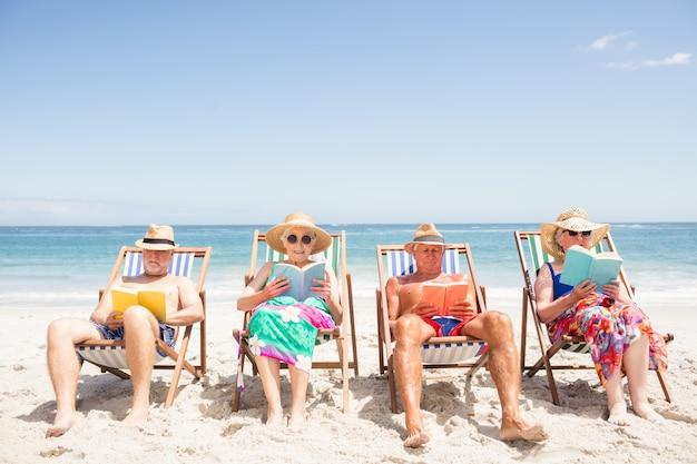 Ältere freunde, die bücher auf strandstuhl lesen