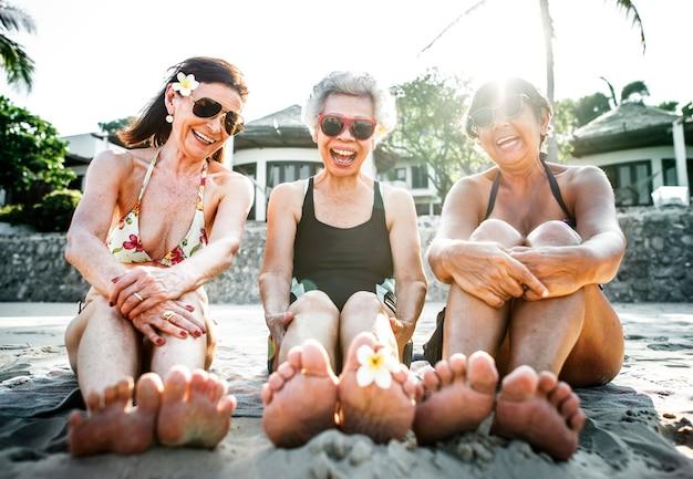 Ältere freunde, die den strand in der sommerzeit genießen