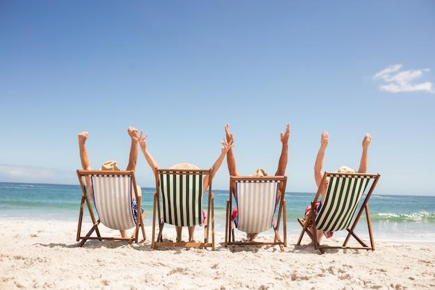 Ältere freunde, die im strandstuhl sitzen