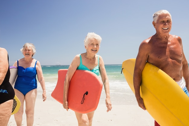 Ältere freunde, die surfbrett halten