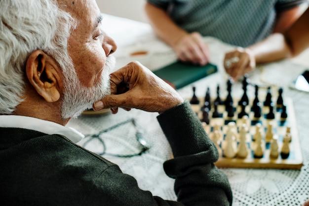 Ältere freunde, die zusammen schach spielen