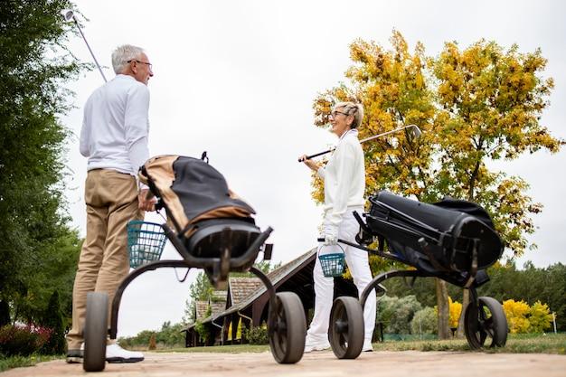 Ältere freunde mit golfausrüstung, die in die grüne zone gehen, um mit dem golfen zu beginnen.