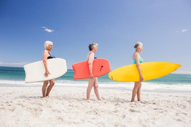 Ältere freundinnen, die surfbrett halten