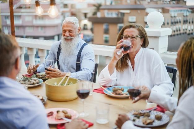Ältere gemischtrassige leute, die spaß beim abendessen auf der terrasse haben