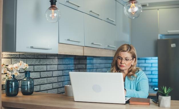 Ältere geschäftsfrau, die am laptop in der küche arbeitet, während sie etwas trinkt