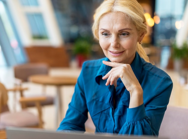 Ältere geschäftsfrau, die am laptop in einem diner arbeitet