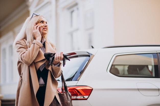 Ältere geschäftsfrau, die am telefon durch ihr elektroauto spricht