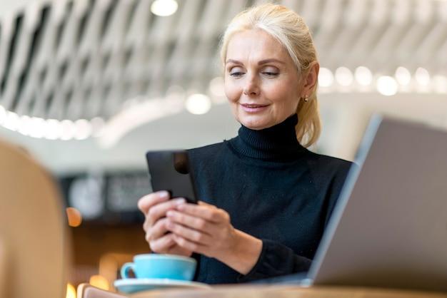 Ältere geschäftsfrau, die an smartphone und laptop arbeitet