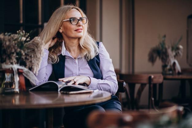 Ältere geschäftsfrau, die außerhalb des cafés sitzt und zeitschrift liest