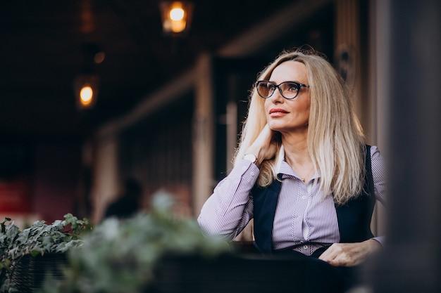 Ältere geschäftsfrau, die außerhalb des cafés sitzt