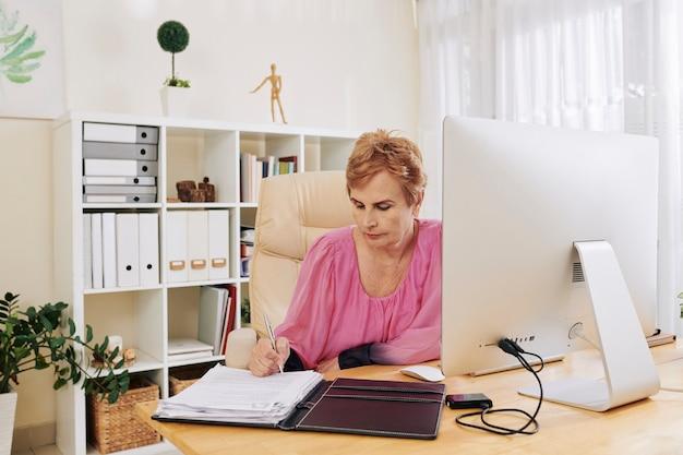 Ältere geschäftsfrau, die dokumente unterschreibt