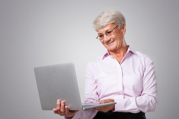Ältere geschäftsfrau, die durch neue technologie arbeitet