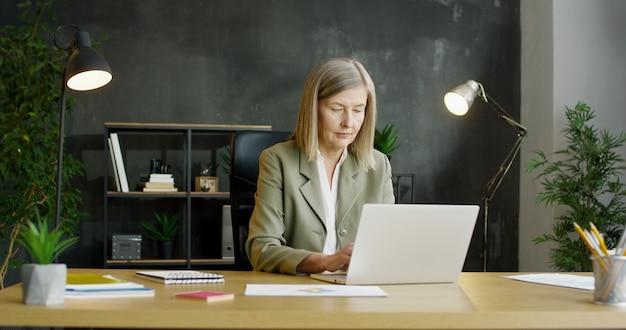 Ältere geschäftsfrau, die im büro sitzt und am laptop arbeitet.