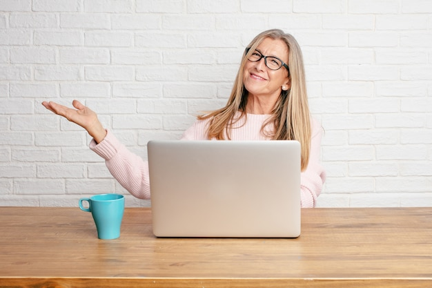 Ältere geschäftsfrau, die mit einem erfüllten ausdruck zeigt einen gegenstand oder ein konzept lächelt