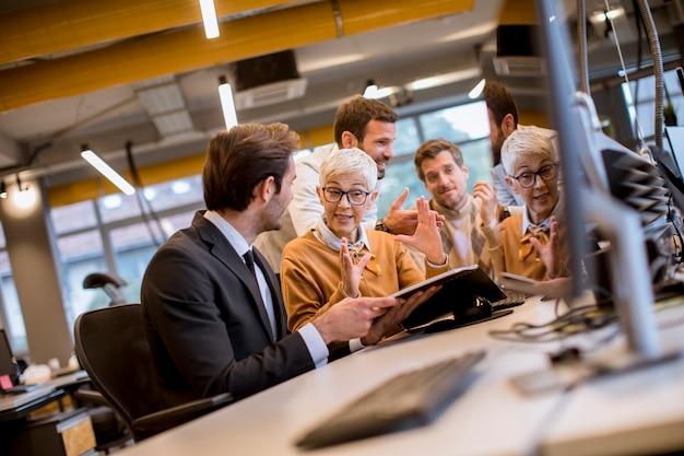 Ältere geschäftsfrau, die zusammen mit jungen geschäftsleuten im büro arbeitet