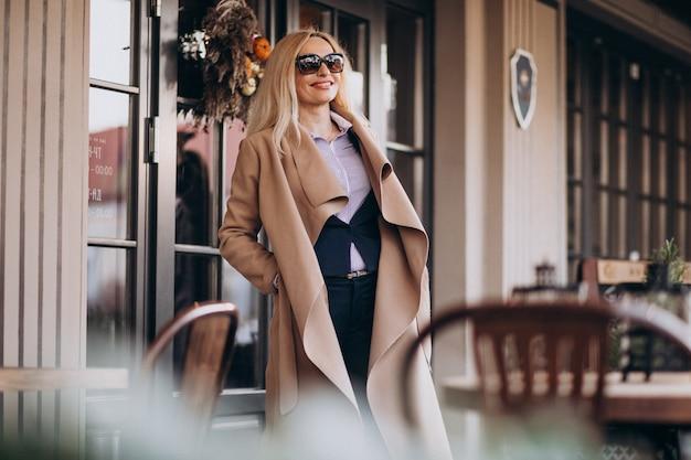 Ältere geschäftsfrau in einem mantel außerhalb des cafés