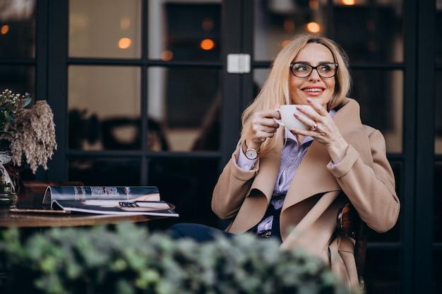 Ältere geschäftsfrau in einem mantel, der außerhalb des cafés sitzt und zeitschrift liest