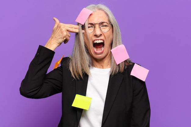 Ältere geschäftsfrau mit klebepfosten. humorvolles geschäftskonzept