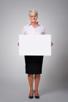 Ältere geschäftsfrau mit leerem whiteboard