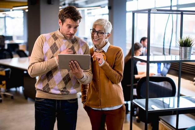 Ältere geschäftsfrau und ihr junger kollege, die im büro mit digitalem tablett stehen
