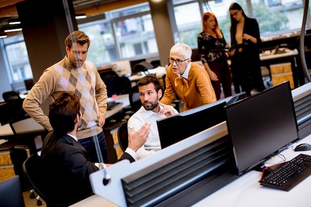 Ältere geschäftsfrau und junge geschäftsleute arbeiten in einem modernen büro