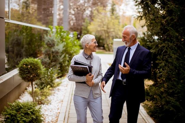 Ältere geschäftsleute, die draußen sprechen und ein dokument im freien besprechen