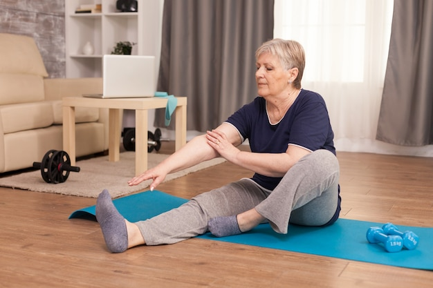 Ältere gesunde frau, die zu hause fitness übt.