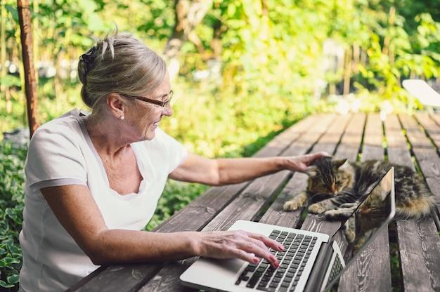 Ältere glückliche ältere frau mit hauptkatze, die online mit laptop im freien im garten arbeitet. heimarbeit